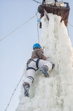 Girl climbs upward on ice climbing competition Royalty Free Stock Photo