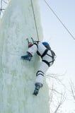 Girl climbs upward on ice climbing competition Stock Photos