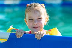 The girl clings to the edge of the pool. She`s swimming in pillows. Stock Photography
