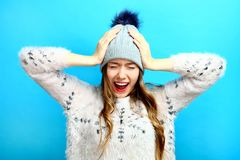 Girl clings to her head and screams. A girl clings to her head and screams on a blue background Royalty Free Stock Photo