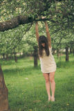 Girl clings to a tree branch Royalty Free Stock Photo