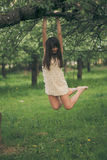 Girl clings to a tree branch Royalty Free Stock Images