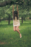 Girl clings to a tree branch Stock Photography