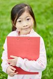 Girl with clipboard during the scavenger hunt. Asian girl with clipboard at the scavenger hunt on a kids birthday stock photos
