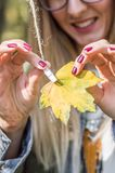Girl clipping the yellow leaf Royalty Free Stock Photography