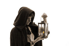 Girl in cloak with a candle-lantern. Isolated on white Royalty Free Stock Photography