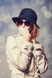 Girl in cloak. Redhead girl in cloak as a spy. Studio shot royalty free stock photos