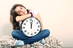 Girl and clock. Young girl sit and holding a clock showing noon or midnight Stock Images