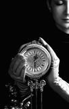Girl with a clock. Monochrome picture of a beautiful girl with a clock (focus on clock Stock Photo