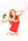 Girl with clock in bedroom Stock Image