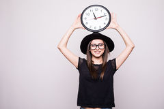 Girl with the clock over head on grey Royalty Free Stock Photos