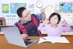 Girl close her ears when get advice from teacher. Female elementary school student closing her ears when get advice from her teacher in the classroom Stock Image