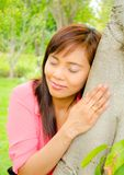 Girl close her eyes and listen sound from a tree Stock Photography