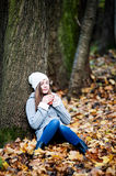 Girl with closed eyes and a cup of tea in her hands. Girl sitting under the tree in the autumn park with closed eyes and a cup of hot tea in her hands Royalty Free Stock Photos