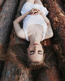 Girl with closed eyes lies on logs Stock Images