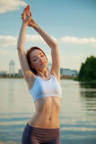 Girl with closed eyes raised his hands in the river. Stock Images