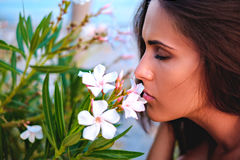 Girl with closed eyes smelling flowers Stock Image