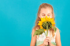 Girl with closed eyes smelling a sunflower Royalty Free Stock Image