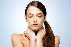 Girl with closed eyes touching her neck Royalty Free Stock Images