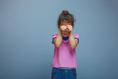 Girl closed her eyes hands on a gray background Royalty Free Stock Images