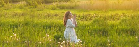 Girl closed her eyes, praying in a field during beautiful sunset. Hands folded in prayer concept for faith stock photography