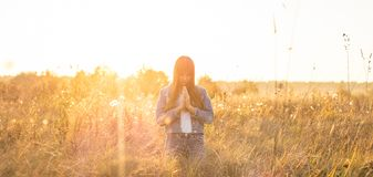 Free Girl Closed Her Eyes, Praying Outdoors, Hands Folded In Prayer Concept For Faith, Spirituality And Religion. Hope, Dreams Concept. Stock Images - 128807694