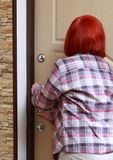 The girl closes the door and looks through the peephole. The girl closes the door from the inside of his apartment. She stands back , holding the door handle and Royalty Free Stock Photos