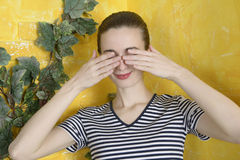 Girl closes her eyes with her hands Royalty Free Stock Photos