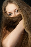 The girl closes long hair the bottom part Stock Photography
