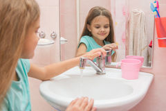 Girl closes after washing the mixer tap in the bathroom Stock Image