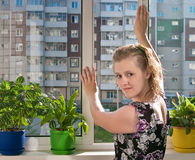 The girl closes a window Stock Photography
