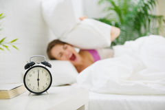 Girl closing ears by pillow to avoid hearing clock Royalty Free Stock Photo