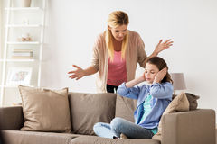 Girl closing ears to not hear angry mother at home stock photography