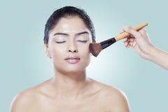 Girl closing her eyes when apply makeup Stock Photos
