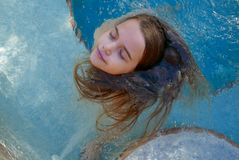 Girl closing her eyes while spinning her long hair around in a spa pool stock photos