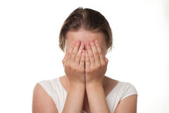 Girl closing her face with hands sorrow or pain emotion. Closeup isolated on the white simple composition stock photos