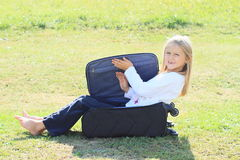 Girl in closing suitcase Royalty Free Stock Images