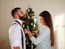 Girl clothe her boyfriend tie on background Christmas tree Stock Image