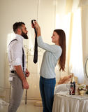 Girl clothe her boyfriend tie in room lit by the sun Royalty Free Stock Image