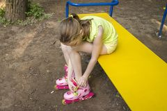Girl clothes rollers sitting on a park bench royalty free stock photo