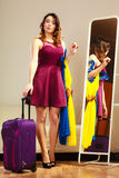 Girl with clothes and suitcase at home, travel Royalty Free Stock Photography
