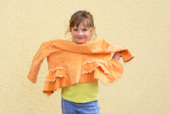 Girl clothing fashion. The girl kept in the hands of trendy orange jacket. The child is photographed near the yellow walls Royalty Free Stock Photography