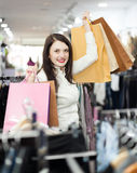 Girl  at clothing  store. Cheerful girl   with shopping bags  at clothing  store Royalty Free Stock Photos