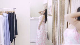 Girl in a clothing store trying on a dress in front of a mirror. Girl looking for a prom dress stock video footage