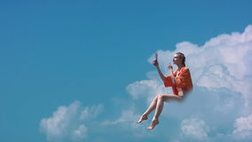 Girl on a cloud. Clear sunny sky. Girl sitting on a cloud and make makeup stock footage