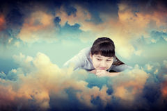 The girl in clouds. The girl the teenager lies in clouds with a smile upon the face and looks in a bottom Stock Photography