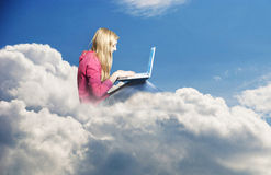 Girl in the clouds with laptop Stock Photo