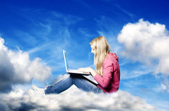 Girl in the clouds with laptop Stock Image