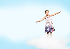 Girl  on clouds and a rainbow Royalty Free Stock Photos