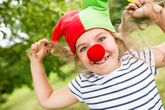 Girl in clown costume with red nose Royalty Free Stock Image